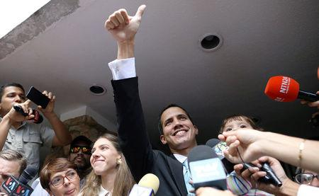 Venezuelan opposition leader and self-proclaimed interim president Juan Guaido reacts next to his wife Fabiana Rosales and while carrying his daughter outside their home in Caracas