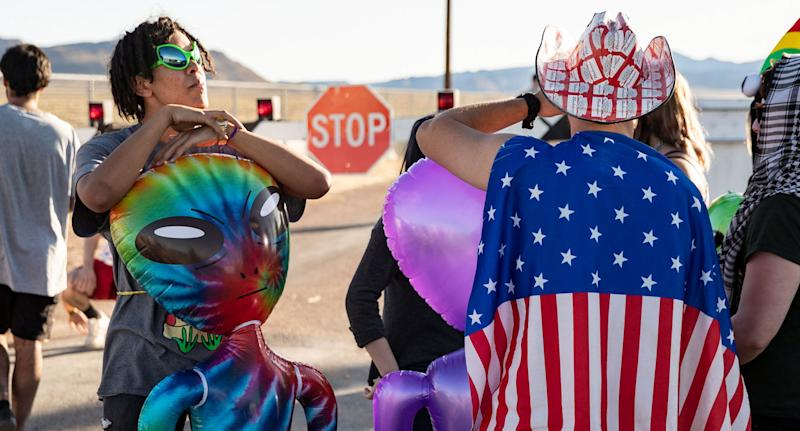 Alien-themed costumes shown on Area 51 raid attendees in the Nevada desert.
