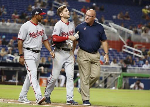 Washington Nationals manager Dave Martinez, left, and Paul Lessard, right, athletic training director, escort Trea Turner to first base after Turner was hit by a pitch during the sixth inning of a baseball game against the Miami Marlins, Tuesday, Sept. 18, 2018, in Miami. (AP Photo/Wilfredo Lee)
