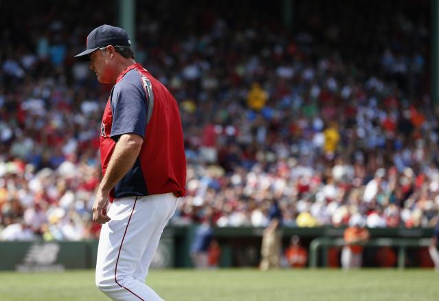 Boston Red Sox manager John Farrell walks to the dugout after arguing with first base umpire Doug Eddings following a grand slam by Houston Astros' Jose Altuve during the ninth inning of a baseball game in Boston, Sunday, Aug. 17, 2014. The Astros won 8-1. (AP Photo/Michael Dwyer)
