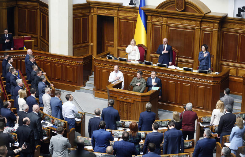 Ukrainian lawmakers sing the national anthem after a vote, in parliament, in Kiev, Ukraine,Thursday, April 25, 2019. The Ukrainian parliament has approved a controversial language law in the largely bilingual country which provides for the mandatory use of the national language by government agencies, local self-government and in other spheres of public life. (AP Photo/Efrem Lukatsky)