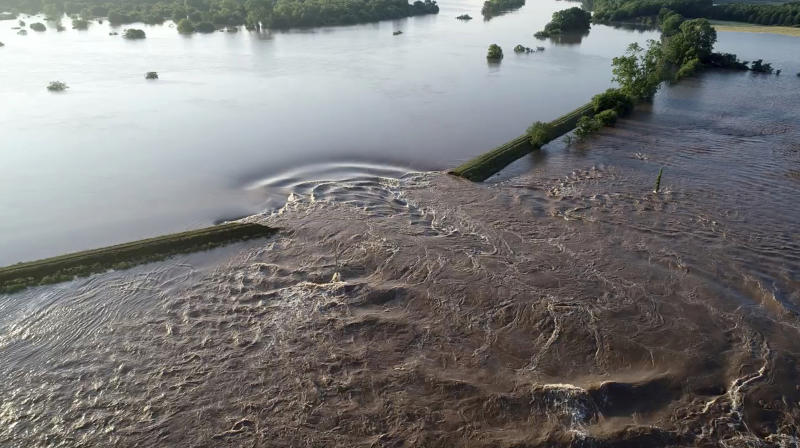 In this aerial image provided by Yell County Sheriff's Department water rushes through the levee along the Arkansas River Friday, May 31, 2019, in Dardanelle, Ark. Officials say the levee breached early Friday at Dardanelle, about 60 miles northwest of Little Rock. (Yell County Sheriff's Department via AP)