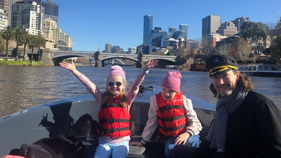 Owain Emslie and his two daughters in a boat in Melbourne.