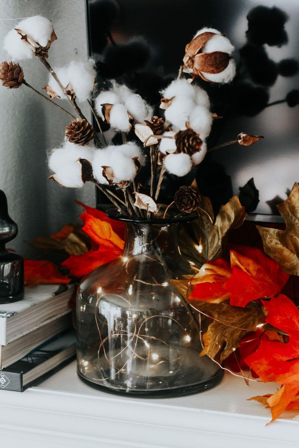 """<p>For an easy piece of fall mantel décor, drop some fairy lights into a smokey gray vase and finish the look with a bouquet of cotton buds. </p><p><strong>Get the tutorial at <a href=""""https://www.thisisourbliss.com/2020/09/16/warm-cozy-fall-mantel/"""" rel=""""nofollow noopener"""" target=""""_blank"""" data-ylk=""""slk:This Is Our Bliss"""" class=""""link rapid-noclick-resp"""">This Is Our Bliss</a>.</strong></p><p><a class=""""link rapid-noclick-resp"""" href=""""https://go.redirectingat.com?id=74968X1596630&url=https%3A%2F%2Fwww.walmart.com%2Fip%2FDecMode-Coastal-Style-Grey-Glass-Clear-Vase-6-W-15-H%2F54320370&sref=https%3A%2F%2Fwww.thepioneerwoman.com%2Fhome-lifestyle%2Fcrafts-diy%2Fg36891743%2Ffall-mantel-decorations%2F"""" rel=""""nofollow noopener"""" target=""""_blank"""" data-ylk=""""slk:SHOP VASES"""">SHOP VASES</a></p>"""