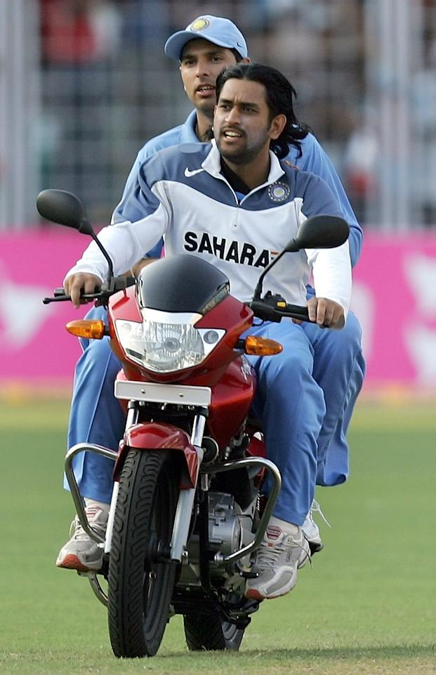 Indian cricketer Mahender Singh Dhoni(R) and teammate Yuvraj Singh ride the man-of-the-match prize-a motorbike awarded to Yuvraj after the third one-day international match between India and England at the Jawaharlal Nehru stadium at Madgaon, 03 April 2006. India won the match by 49 runs to take a 2-0 lead over England in the seven match one-day series.   AFP PHOTO/ Indranil MUKHERJEE