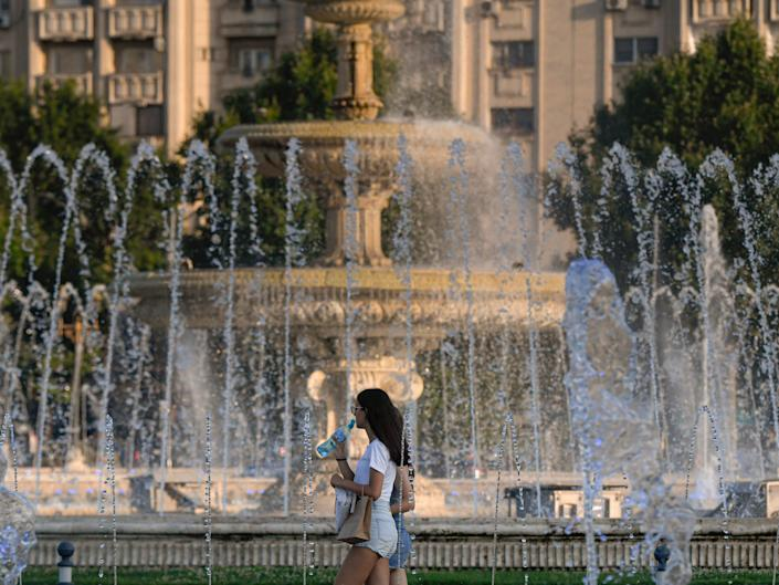 Woman walking in front of fountain