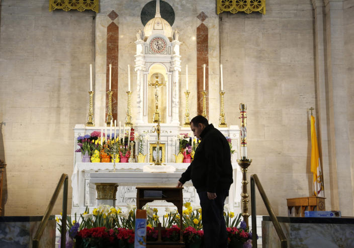 In this April 19, 2020, photo, the Rev. Joseph Dutan, 32, stands near the altar as he prepares for a virtual holy hour livestreamed after Sunday Mass at St. Brigid Church in the Brooklyn borough of New York. (AP Photo/Jessie Wardarski)