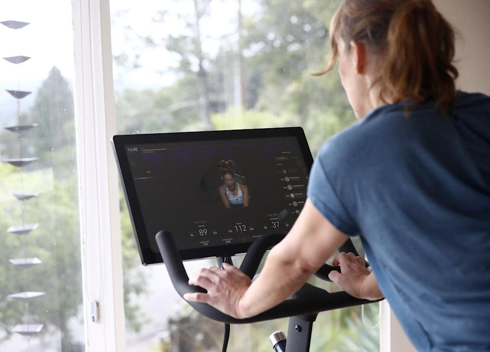 SAN ANSELMO, CALIFORNIA - APRIL 06:  Becky Friese Rodskog rides her Peloton exercise bike at her home on April 06, 2020 in San Anselmo, California.  More people are turning to Peloton due to shelter-in-place orders because of the coronavirus (COVID-19). The Peloton stock has continued to rise over recent weeks even as most of the stock market has plummeted. Peloton announced that they will temporarily pause all live classes until the end of April because an employee tested positive for coronavirus (COVID-19).  (Photo by Ezra Shaw/Getty Images)