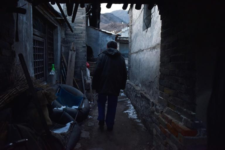 A former coal miner walks to his home in a village outside the Datai coal mine in Mentougou, west of Beijing, in December 2019, as Beijing curbs the heavily polluting energy