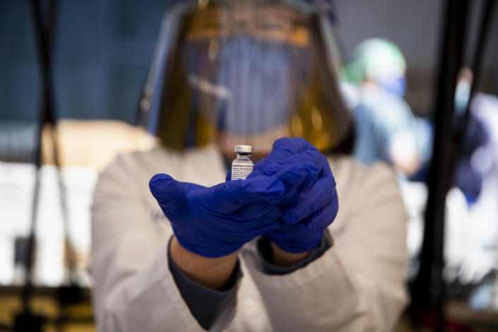 A health care worker at UCI Medical Center displays a vial of the Pfizer-BioNTech COVID-19 vaccine in Orange, Calif., Wednesday, Dec. 16, 2020. (Jenna Schoenefeld/The New York Times)