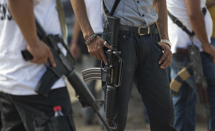 """Armed men belonging to the Self-Defense Council of Michoacan (CAM) stand guard at a checkpoint set up by the vigilante group in La Mira on the outskirts of the seaport of Lazaro Cardenas in western Mexico, Friday, May 9, 2014. Starting Saturday, a federal commissioner now in charge of the violence-plagued state hopes to end the """"wild west"""" chapter of the vigilante movement, in which civilians went to battle against cartel members for towns in the rich farming area called the """"Tierra Caliente,"""" or Hot Land. (AP Photo/Eduardo Verdugo)"""
