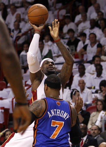 Miami Heat's LeBron James, left, shoots and is fouled by New York Knicks' Carmelo Anthony (7) in the first half during an NBA basketball game in the first round of the Eastern Conference playoffs in Miami, Saturday, April 28, 2012. (AP Photo/Lynne Sladky)