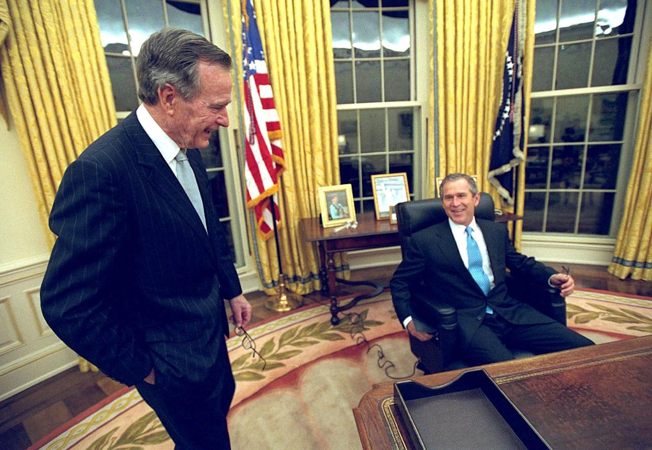 President George W. Bush talks to his father, former President Bush as he sits at his desk in the Oval Office for the first time on Inaugural Day, Jan. 20, 2001. (AP Photo/Eric Draper, White House)