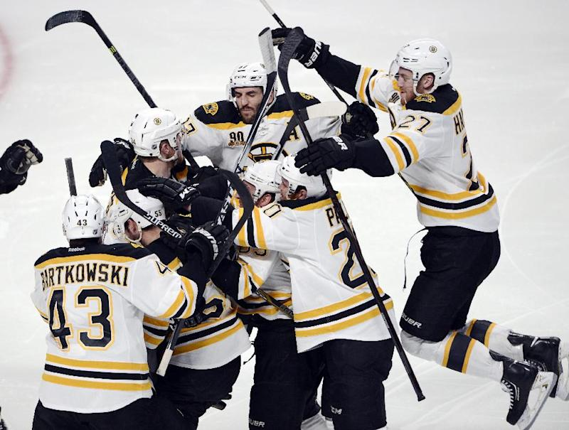 Boston Bruins' Matt Fraser is mobbed by teammates after scoring the game winning goal against the Montreal Canadiens during the first overtime period in Game 4 in the second round of the NHL Stanley Cup playoffs Thursday, May 8, 2014, in Montreal