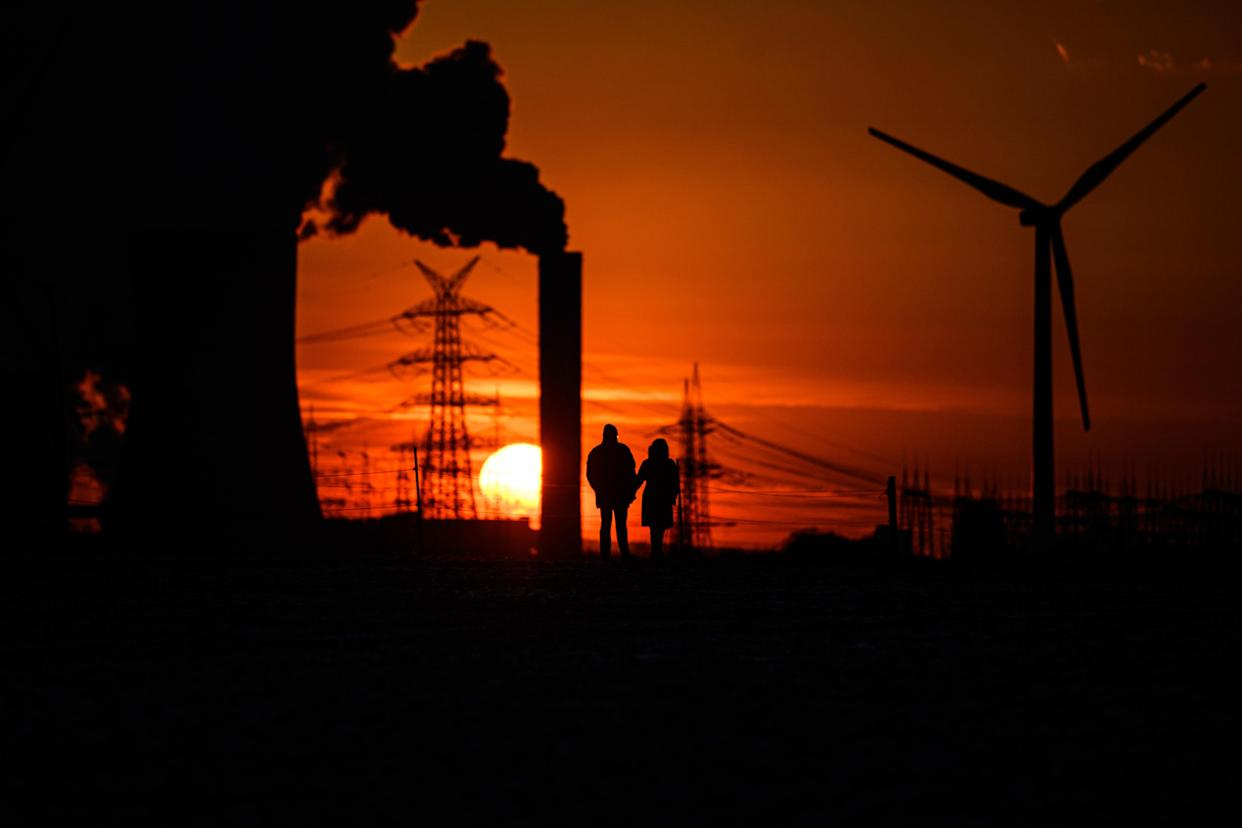 Two people stand before a sunset near steam rising from cooling towers of a power plant