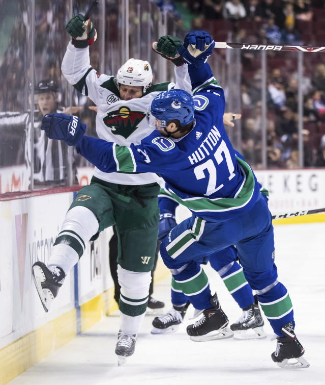 Vancouver Canucks' Ben Hutton (27) and Minnesota Wild's Matt Hendricks (15) collide during the first period of an NHL hockey game, Tuesday, Dec. 4, 2018, in Vancouver, British Columbia. (Darryl Dyck/The Canadian Press via AP)