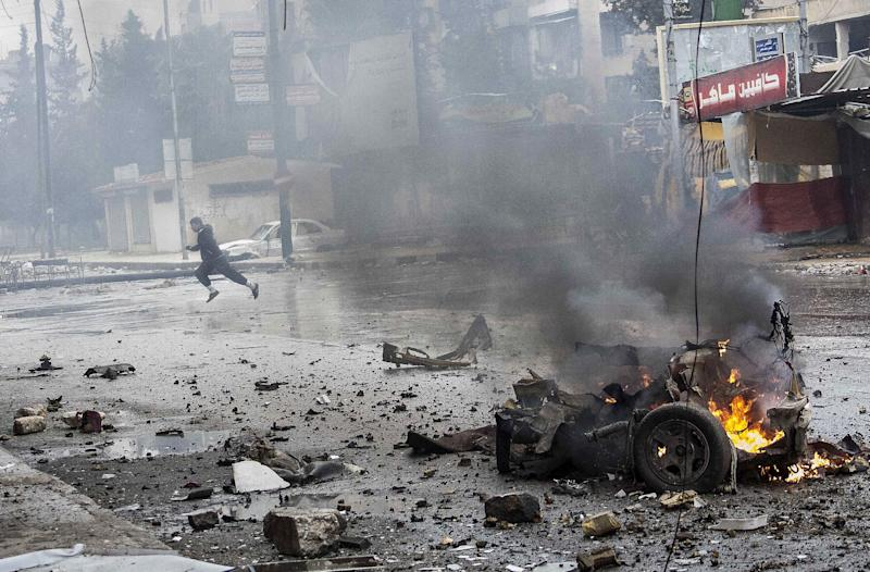 In this Monday, Dec. 17, 2012 photo, a boy runs for cover after a mortar shell hit a street killing several people in the Bustan Al-Qasr district of Aleppo, Syria. (AP Photo/Narciso Contreras)