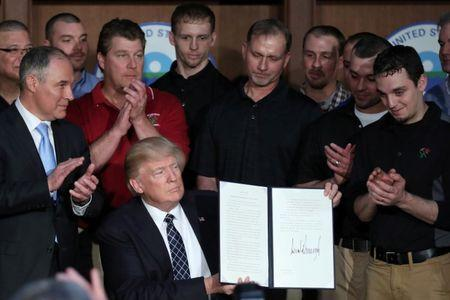 """U.S. President Donald Trump holds up an executive order on """"Energy Independence,"""" eliminating Obama-era climate change regulations, during a signing ceremony at the Environmental Protection Agency (EPA) headquarters in Washington, U.S."""