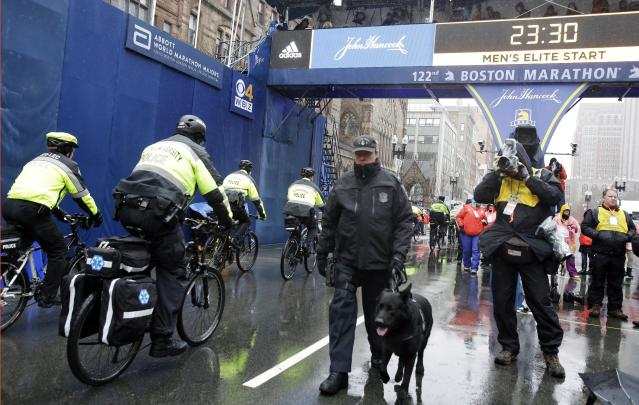 Bicycle-mounted police officers pass a Boston Special Operations K-9 police officer and his dog as they patrol at the finish line before the 122nd Boston Marathon on Monday, April 16, 2018, in Boston. (AP Photo/Elise Amendola)