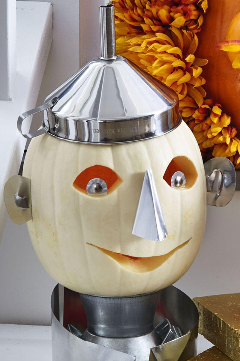 <p>He may not have a heart, but Dorothy's Tin Man is gleaming thanks to a milk-jug collar, a shiny funnel hat, and foil eyes, ears, and nose. First, hollow out tall white pumpkin from top (make hole smaller than opening of funnel). </p><p>Carve eyes and mouth. Cut pupils, nose, and ears from 36-gauge foil sheet roll; hot-glue in place. Sit pumpkin on metal milk jug or can. Cut and curl collar around vessel; place funnel on top for hat. </p>
