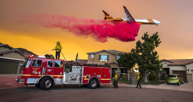 <p>A plane drops fire retardant behind homes along McVicker Canyon Park Road in Lake Elsinore, Calif., as the Holy Fire burned near homes on Wednesday, Aug. 8, 2018. (Photo: Mark Rightmire/The Orange County Register via AP) </p>