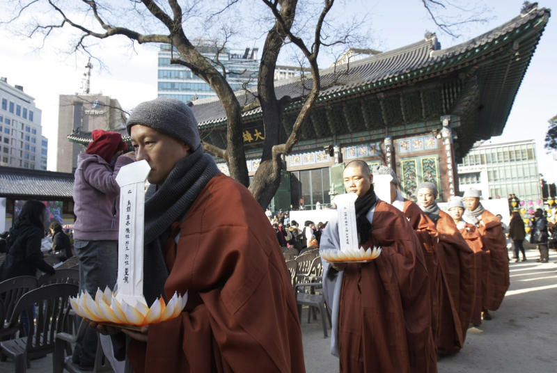 South Korean Buddhist monks with the ancestral tablets of the victimized livestock march during a memorial service for them slaughtered by foot-and-mouth disease at the Jogye Temple in Seoul, South Korea, Wednesday, Jan. 19, 2011. Hundreds of Buddhist monks and faithful gathered at South Korea's main temple to offer prayers for the nearly two million livestock slaughtered in the country's worst outbreak of foot-and-mouth disease.(AP Photo/Ahn Young-joon)