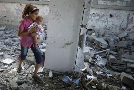 A Palestinian girl holding her sister walks through debris near remains of a mosque, which witnesses said was hit by an Israeli air strike, in Beit Hanoun in the northern Gaza Strip August 25, 2014. REUTERS/Mohammed Salem