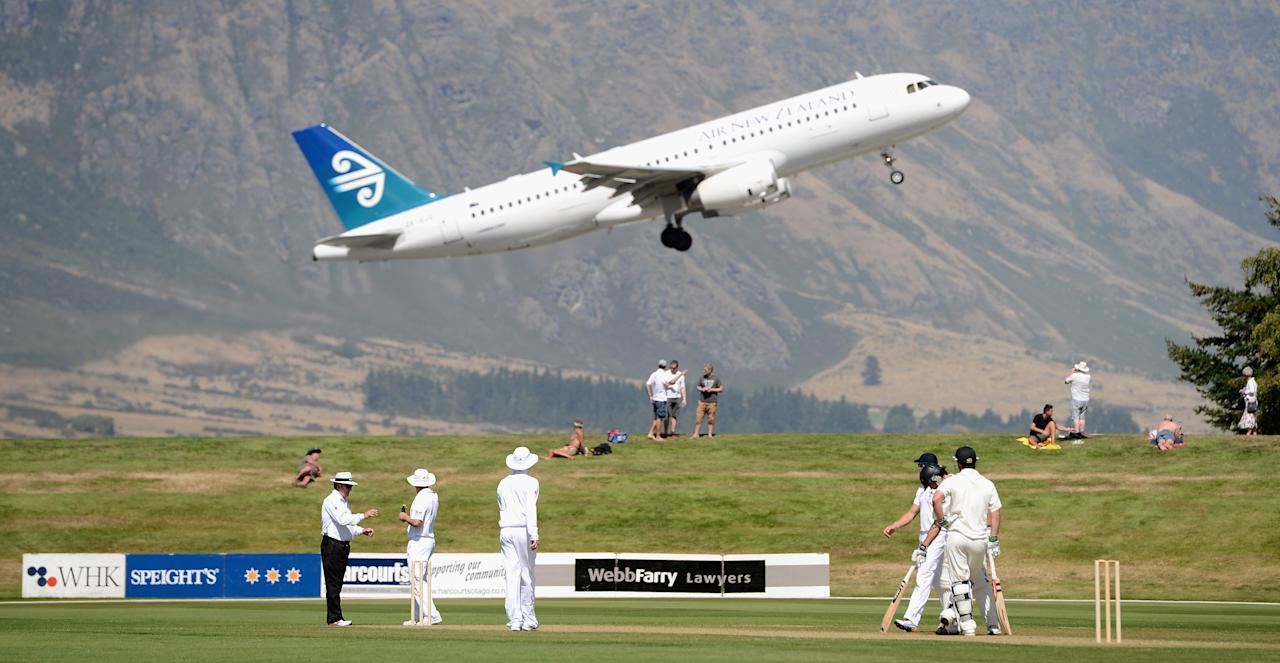QUEENSTOWN, NEW ZEALAND - FEBRUARY 28:  England fielders watch on a Air Zealand plane flys overhead during day two of the International tour match between the New Zealand XI and England at Queenstown Events Centre on February 28, 2013 in Queenstown, New Zealand.  (Photo by Gareth Copley/Getty Images)