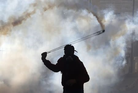 A Palestinian protester uses a slingshot to throw back a tear gas canister fired by Israeli troops during clashes, following the funeral of Palestinian minister Ziad Abu Ein near the West Bank city of Ramallah December 11, 2014. REUTERS/Ammar Awad