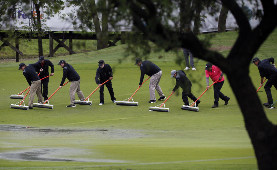 Course workers squeegee the 18th fairway following a weather delay during the final round of the AT&T Byron Nelson golf tournament in McKinney, Texas, Sunday, May 16, 2021. (AP Photo/Ray Carlin)