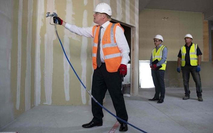 The PM helped on a construction site yesterday - but warned of a long way to 'economic vitality' - MATTHEW HORWOOD /AFP
