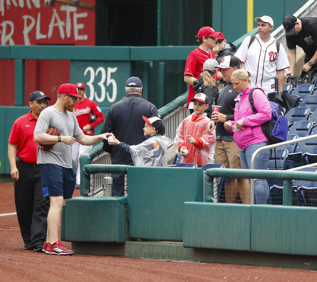Washington Nationals relief pitcher Sean Doolittle, left, stops to sign autographs after it was announced that both of today's interleague baseball games against the New York Yankees have been postponed due to inclement weather, Wednesday, May 16, 2018, at Nationals Park in Washington. Both games have been rescheduled for June 18, 2018. (AP Photo/Pablo Martinez Monsivais)