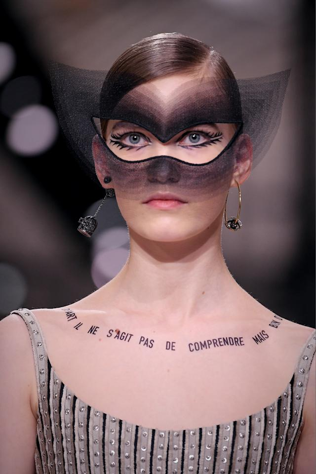 "<p>A quote by French poet André Breton was ""tattooed"" across a model's chest, which read, <em>""Au départ il ne s'agit pas de comprendre mais bien d'aimer,""</em> which translates to, ""Initially, it's not about understanding, but about loving."" (Photo: Getty) </p>"
