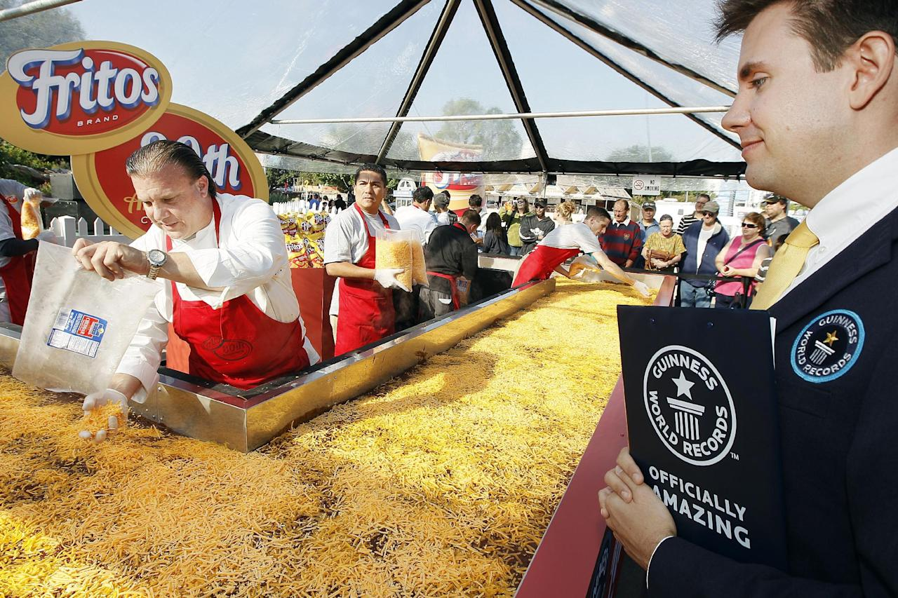Michael Empric, Guiness Worlds Records Adjudicator, looks on as chef Drew Deckman adds cheese while preparing the World's Largest Fritos Chili Pie at the State Fair of Texas, on Monday, Oct. 1, 2012 in Dallas. The pie weighed in at 1,325 pounds, and was created to celebrate the 80th anniversary of Fritos Corn Chips. (Photo by Brandon Wade/Invision for Frito-Lay/AP Images)