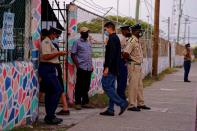 Police officers stand outside a polling station during the election for a new prime minister, in Belize City