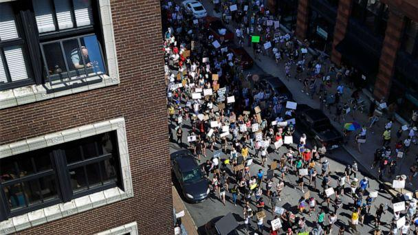 PHOTO: A person, upper left, holds a phone while watching from a window as protesters march in the street below Sunday, June 7, 2020, in St. Louis, Mo. (Jeff Roberson/AP Photo)