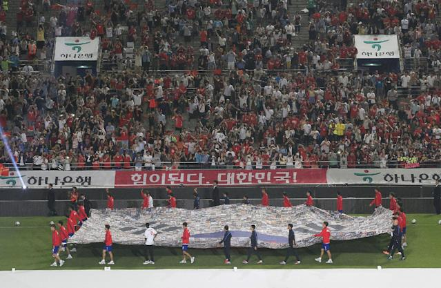 South Korea's national soccer team players carry a national flag during a send-off ceremony to the World Cup in Brazil after a friendly soccer match against Tunisian at World Cup stadium in Seoul, South Korea, Wednesday, May 28, 2014. South Korea will play against Belgium, Russia and Algeria in Group H of the World Cup 2014 in Brazil. (AP Photo/Ahn Young-joon)