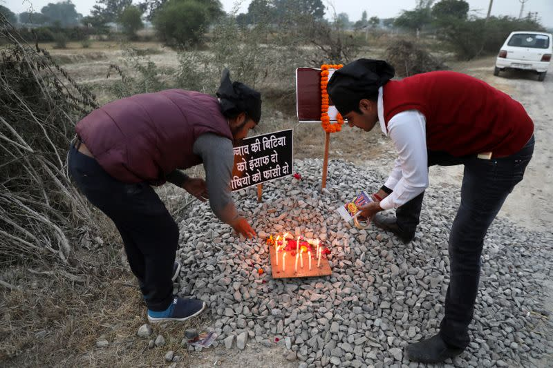 Students light candles next to placards near the spot where a 23-year-old rape victim was set on fire by a gang of men, which included her alleged rapists, in Unnao