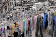 """A woman works in the automated sortation section at Rent the Runway's """"Dream Fulfillment Center"""" in Secaucus, New Jersey"""
