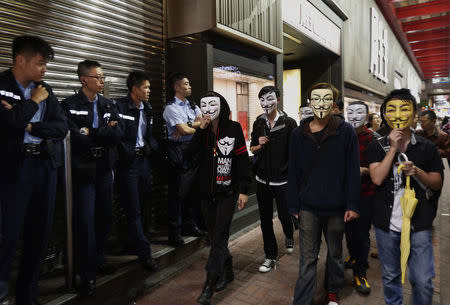 Pro-democracy protesters wearing Guy Fawkes masks walk past policemen on a road occupied by protesters as part of the Occupy Central civil disobedience movement at Mongkok shopping district November 5, 2014, the day marking Guy Fawkes Night. REUTERS/Bobby Yip