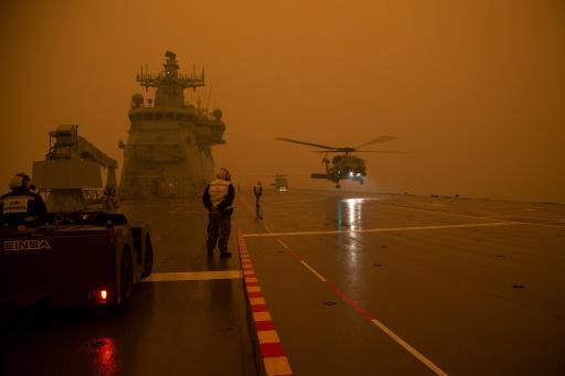 Royal Australian Navy MH-60R Seahawk helicopters taking off from HMAS Adelaide as part of bushfire relief operations -- Australia has made its biggest-ever callup of military reserves in living memory, to help emergency services workers