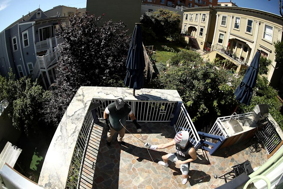 SAN FRANCISCO, CALIFORNIA - MAY 15:  Alexander Massialas (right) trains with his father and coach, Greg Massialas, on their back porch on May 15, 2020 in San Francisco, California. Alexander was on the 2012 and 2016 US Olympic Fencing Team and had planned on being in Tokyo this summer for the 2020 Summer Olympics. He won the silver medal in individual foil and a bronze medal in the team event at the 2016 Olympics. Greg was a member of the 1980, 1984, and 1988 US Olympic Team and is now the national coach for the United States foil team.  Athletes across the globe are now training in isolation under strict policies in place due to the Covid-19 pandemic.  Massialas is now focused on staying in shape and getting ready for the Olympics in Tokyo in 2021.  (Photo by Ezra Shaw/Getty Images)