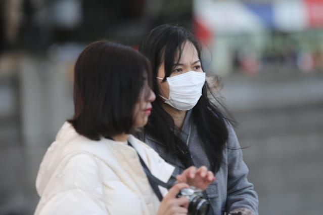 A woman wears a medical mask in a street in London (Anadolu Agency via Getty)