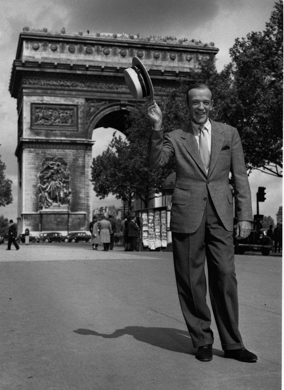 <p>Yet another historic snap from the filming of <em>Funny Face</em>. Here, Fred Astaire tips his cap in front of the Arc de Triomphe.</p>