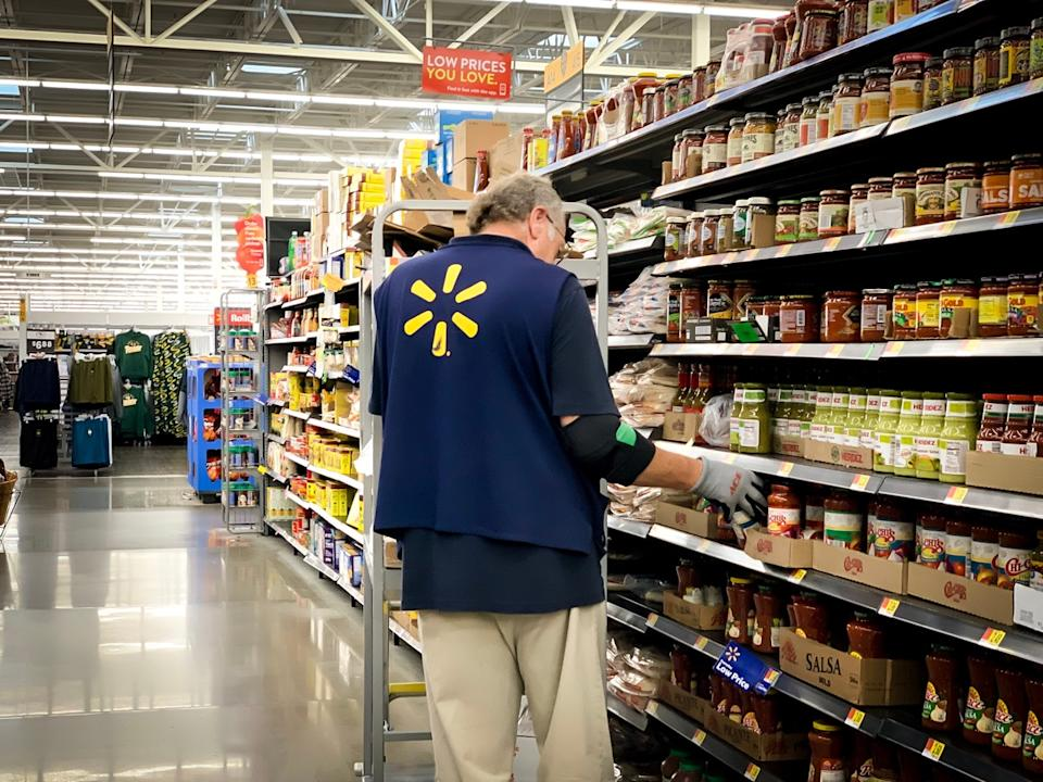 older male walmart employee stocking shelves