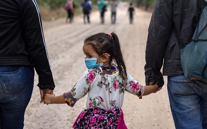 An immigrant child glances back towards Mexico after crossing the border into the United States - Getty