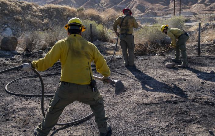 An engine crew looks for any remaining hot spots from the Tick Fire, Thursday, Oct. 25, 2019, in Santa Clarita, Calif. An estimated 50,000 people were under evacuation orders in the Santa Clarita area north of Los Angeles as hot, dry Santa Ana winds howling at up to 50 mph (80 kph) drove the flames into neighborhoods (AP Photo/ Christian Monterrosa)
