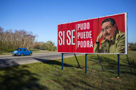 """FILE - In this April 18, 2018 file photo, a car drives by a billboard that reads in Spanish """"Yes we could, yes we can, yes we will"""" alongside a picture of Cuban President Raul Castro on the outskirts of Havana, Cuba. On Friday, April 16, 2021, Castro formally announced he'd step down as head of the Communist Party, leaving Cuba without a Castro in an official position of command for the first time in more than six decades. (AP Photo/Desmond Boylan, File)"""