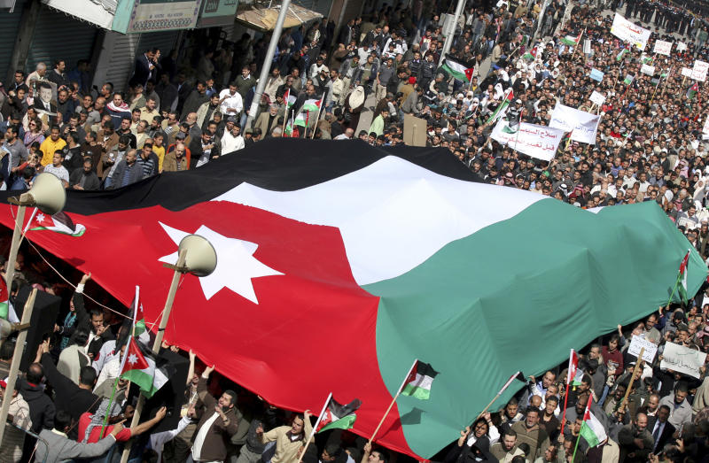 """Jordanian supporters of the Islamic Action Front, carry a giant national flag as they march during a protest in Amman, Jordan, Friday, Feb. 25, 2011. The leader of Jordan's largest opposition group has warned that citizens' patience is wearing thin with the government's """"slow"""" moves toward reform. Hamza Mansour spoke to 4,000 Jordanian protesters, the largest crowd yet to take to the streets of downtown Amman for the pro-reform cause. Jordanians have now been holding protests for eight consecutive Fridays. (AP Photo/Nader Daoud)"""