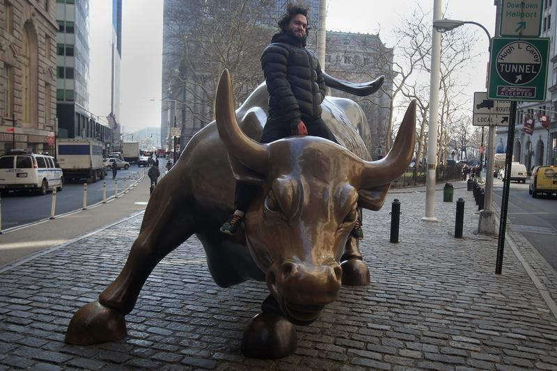 """A tourist mounts the """"Charging Bull"""" statue as he poses for a photo near Wall Street, in the Manhattan borough of New York"""